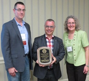 Michael Dame (L) and Cynthia Goodman (R) present Guy Smagghe with the Distinguished Scientist Award.