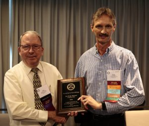 John Harbell thanks Fredy Altpeter for his work as the 2019 Program Committee Chair